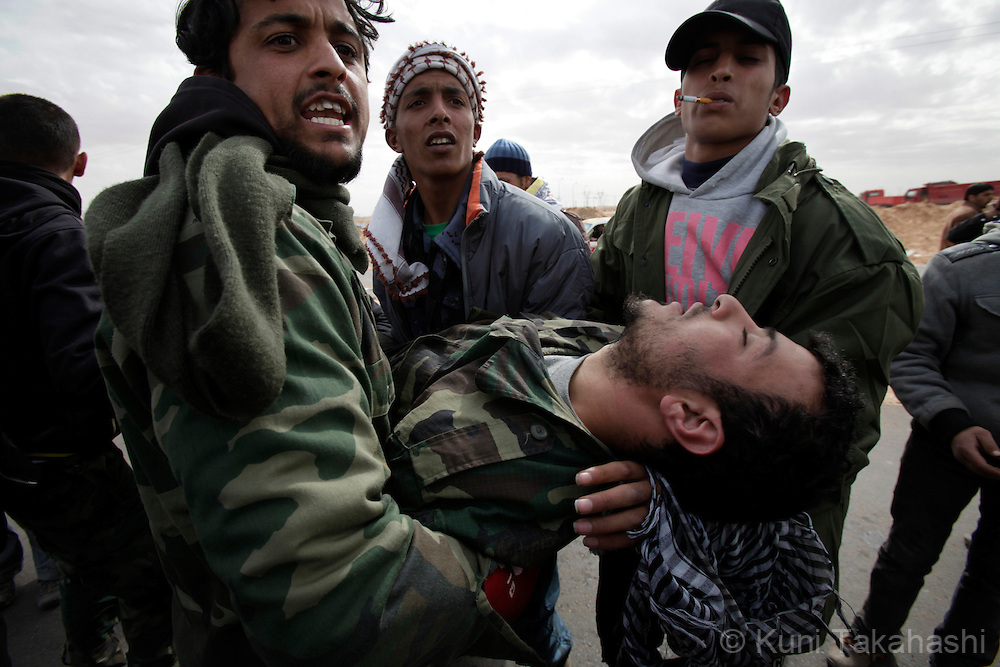Injured rebel soldier agasint Col. Muammar Gaddafi is carried to ambulance in Ras Lanuf on March 10, 2011. The government military and rebels kept fighting for taking control of the town for the last three days. Photo by Kuni Takahashi