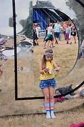 Latitude Festival, Henham Park, Suffolk, UK July 2019. Girl reading a book on one of the giant letters