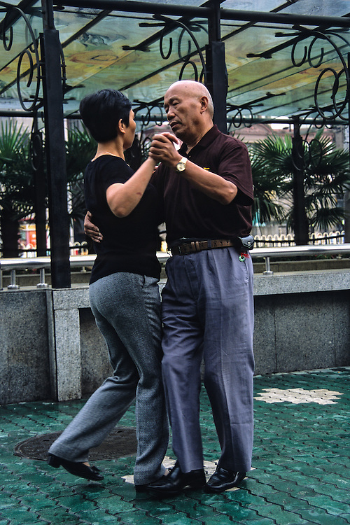 A couple gets their morning exercise by ballroom dancing on the sidewalk.