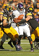 October 26 2013: Northwestern Wildcats running back Stephen Buckley (8) is hit by Iowa Hawkeyes linebacker James Morris (44) and Iowa Hawkeyes defensive back Tanner Miller (5) during the fourth quarter of the NCAA football game between the Northwestern Wildcats and the Iowa Hawkeyes at Kinnick Stadium in Iowa City, Iowa on October 26, 2013. Iowa defeated Northwestern 17-10 in overtime.