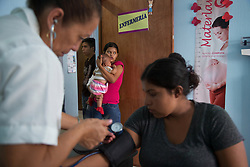 "The vitals of young mothers are taken at the San Benito Youth Clinic. ""To see a girl having to deal with a baby, it is as if she was playing with dolls [but she isn't]. To me that's shocking,"" said Dr. Sayda Acosta, pediatrician and San Benito Youth Clinic director."