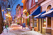 Beautiful old buildings and storefronts line lower Maine Street in Brunswick Maine at night after a small snowfall.