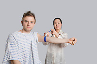 Portrait of male patient with doctor preparing him for a blood test