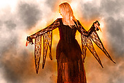 Flames engulf a young woman in a Digitally enhanced image of a model wearing Gothic style clothes and lace dress