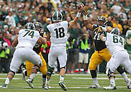 October 6 2013: Michigan State Spartans quarterback Connor Cook (18) passes over Iowa Hawkeyes defensive lineman Carl Davis (71) as he is blocked by Michigan State Spartans guard Blake Treadwell (64) during the first quarter of the NCAA football game between the Michigan State Spartans and the Iowa Hawkeyes at Kinnick Stadium in Iowa City, Iowa on October 6, 2013.