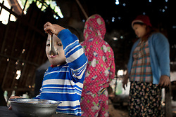 The youngest son of Ko Aung Mgo having breakfast while the family is making the palm sugar.<br /> At Ka Myaw Gyi village in the outskirts of Dawei, Myanmar.