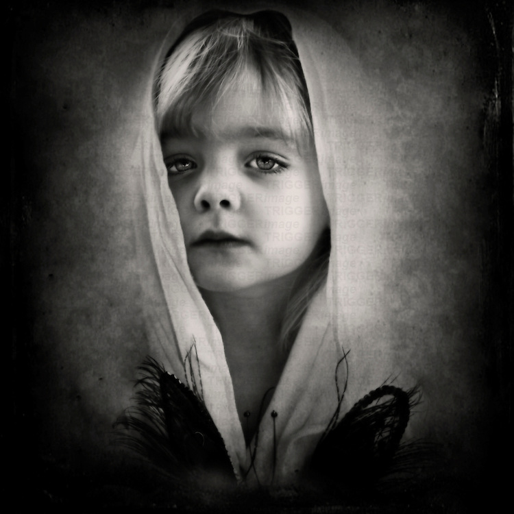 A young girl looking at the camera with a veil over her head