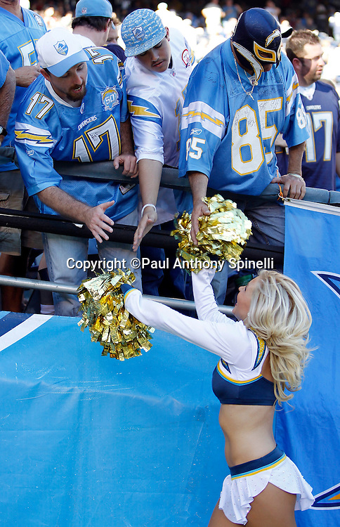 A San Diego Chargers cheerleader high fives fans during the NFL week 14 football game against the Kansas City Chiefs on Sunday, December 12, 2010 in San Diego, California. The Chargers won the game 31-0. (©Paul Anthony Spinelli)