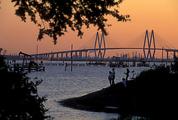 Sunset silhouette of the Fred Hartman Bridge at the Port of Houston with people fishing at the Goose Creek Oil Field.