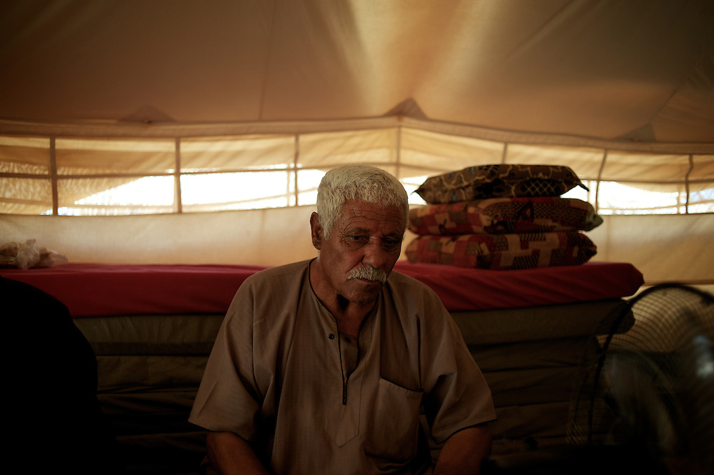 August 08, 2013 - Zaatari, Jordan: Mahmoud Amarin, a 70 year old syrian bus driver from Daraa city, sits in his tent at Zaatari refugee camp, in northern Jordan. Mr. Amarin fled the fighting in Syria one year ago, when his house got shelled by the regime forces. Like many other refugees in Zaatari, Mr. Amarin lost two of his children during the attack to his village, leaving behind all his worldly possessions. He lives now at the camps with his wife and two children, and depends uniquely on basic aid provided by international Non-Governmental Organisations. Mr. Amarin intends to go back to his hometown soon, due to the harsh life refugees endure at camp. Zaatari camp, home to more than 120,000 people who in the past year have fled the conflict in Syria, become the fourth largest city in Jordan and the world's second largest refugee camp behind Dadaab in eastern Kenya. Most of its residents came from Daraa, a city about 30Km away in Syria, rich with businessmen thanks to a long history of cross-border trade with Jordan. (Paulo Nunes dos Santos/Al Jazeera)
