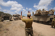 UNSPECIFIED, ISRAEL - JULY 17, 2014: An Israeli soldier directs a Merkava tank, at an army deployment area near Israel's border with the Gaza Strip, on July 17, 2014. Photo by Gili Yaari.