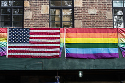 "August 26, 2017 - New York City, New York, United States of America - American and Pride flags together across from the Stonewall Inn. Dozens demonstrated for Kiwi Herring, a 30 year old trangender woman that was shot and killed by St. Louis police after a call from a neighbor. The demonstration eventually became a march that snaked through lower Manhattan, making stops at restaurants to deliver the message to the patrons.  At least one verbal altercation transpired. The family of Herring alleges that she was the victim of long-term harassment by a ""homophobic"" neighbor, while the police allege that she held a knife and injured at least one officer with it.  Prior to the fatal incident, there was another knife incident on the premises involving Herring and a neighbor.  ..Currently, police are investigating and if non-lethal methods were used before the fatal shooting.  The Human Rights Campaign, a gay rights NGO, has stated that this is the 18th transgender killing this year, with nearly all the victims being people of color, and nearly all having been black.  Furthermore, just one day prior, Trump signed the bill banning transgender people from serving in the military. (Credit Image: © Sachelle Babbar via ZUMA Wire)"
