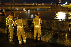 © Licensed to London News Pictures. 13/01/2017. Great Yarmouth, UK. Fire brigade and military personnel watch as the swollen River Bure reaches high tide in the centre of Great Yarmouth. Environment Agency warnings are in place in some coastal areas ahead of the late night high tides. Photo credit: Peter Macdiarmid/LNP