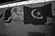 The Turkish flag painted next to Syrian flag shaped as a bird, on the wall of a shelter used for making falafel in Reyhanli refugee camp in Hatay, southern Turkey. 14th March 2012. ENN Photo/Bradley Secker