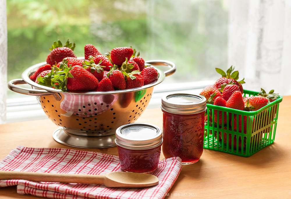 Fresh strawberries and strawberry jam in glass jam jars.