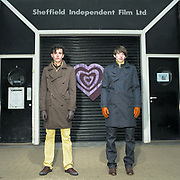 Two young men standing straight in front of the Sheffield Independent Film ltd.