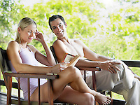 Couple sitting on terrace woman reading book