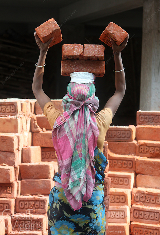 Woman laborer carrying bricks on building site in Silliguri, West Bengal, India