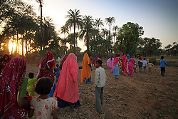 People walk to gather water in jars as part of a wedding ritual before the nuptials of three young girls: Radha Bhamwari, 15-years-old, Gora Bhamwari, 13-years-old and Rajni Bhamwari, 5-years-old. Rajasthan, India on April 26, 2009.