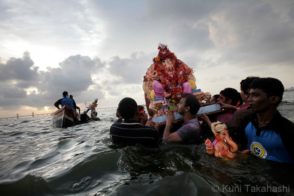 Hindu devotees immerse ganesha idols into the sea in Mumbai, India on Sep 16, 2010 on the 6th day of Ganpati festival. The 10-day hindu festival, celebrating the birthday of Lord Ganesha who is widely worshiped as the god of wisdom, prosperity and good fortune, attracts tens of thousands people.<br /> Photo by Kuni Takahashi