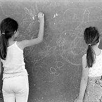 Girls writing on a wall with chalk...During the summer1999, over 245,000 Serbs and Roms fled to Serbia and Montenegro from or within Kosovo in fear of reprisals from the majority Albanian population, after NATO air strikes had forced the withdrawal of Yugoslav. In 2003, less than 2% of them had returned and a large number of these internally displaced persons (IDPs) were still living in camps in very difficult conditions..In addition, around 5,000 IDPs, mainly of Roma ethnicity, are living in unrecognized collective centres, makeshift huts, corrugated metal containers and other substandard shelters. .This work  was meant to look at how the life of children and young adults is affected by the fact that they are IDPs. I asked myself more specifically what would be different for these children/young adults from the 'normal' people of their age as far as education, health, social life, family, 'love' life and leisure are concerned. ..Petites filles écrivant sur un mur avec des craies...Pendant l'été 1999, plus de 245 000 serbes et roms ont fuit le Kosovo pour chercher refuge en Serbie ou au Montenegro, par peur de représailles de la part de la majorité de la population albanaise après que les forces de l'OTAN aient forcé l'armée yougoslave à se retirer. En 2003, moins de 2% d'entre eux étaient rentrés chez eux et le plus grand nombre de ces 'déplacés' (IDPs) vivaient encore dans des centres d'accueil dans des conditions très difficiles..Environ 5 000 IDPs, la plupart romas, vivent dans des centres non reconnus faits de containers ou d'abris de fortune. .Ce travail s'est focalisé sur les jeunes IDPs, sur les conséquences de leur état de 'déplacés' sur leur vie et plus particulièrement dans les sphères concernant l'éducation, la santé,  la vie sociale, la vie de famille, la vie amoureuse et les loisirs..