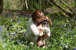 © Licensed to London News Pictures. 21/04/2018. Vigo, UK. Antonella Stacchiotti from Gravesend with one year old Cockapoo Pip enjoying Kent bluebells.  The bluebells are now in full bloom at Trosley Country Park Photo in the village of Vigo near to Gravesend in Kent. credit : Rob Powell/LNP