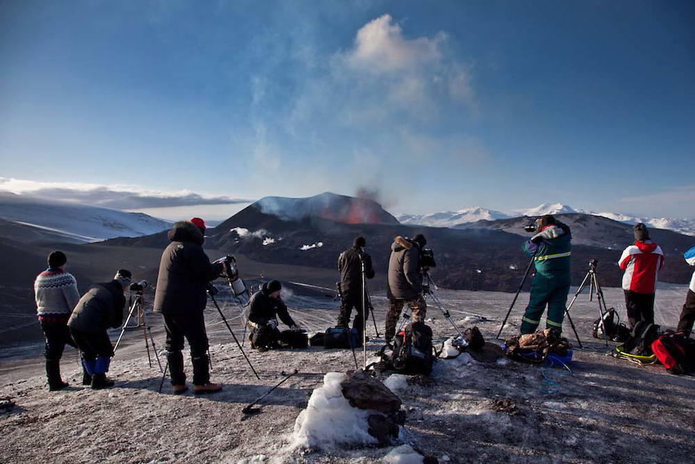 A small army of photographers shooting at a Volcanic eruption in Iceland