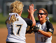 9 OCT. 2010 -- ARNOLD, Mo. -- Oakville High School pitcher Remy Edwards (12) is congratulated by teammate Adrianna Wegmann (17) after striking out a player from Cor Jesu Academy at the MSHSAA Class 4 Distirct 2 softball championships at Fox High School in Arnold, Mo. Saturday, Oct. 9, 2010. The Tigers topped Cor Jesu 3-0 to advance in the playoffs. Image © copyright 2010 Sid Hastings.