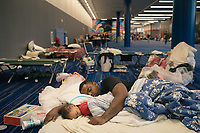 Gerald Sam embraces his one-year-old son Gavir Sam as they try to sleep at the George R. Brown Convention Center in downtown Houston. Sam and his wife have spent two days in the shelter with their four children. They plan to leave today.
