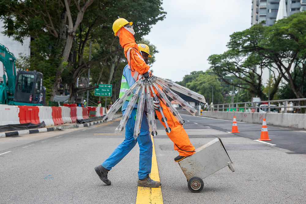 A construction worker relocates a safety mannequin on Thomson Road, Novena in Singapore.
