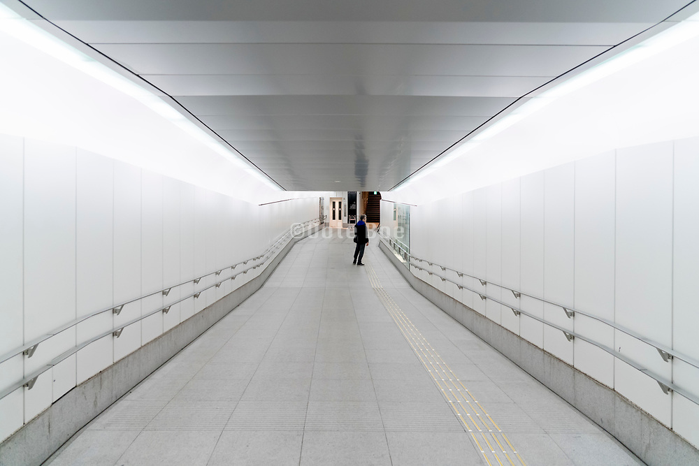 long brightly lighted underground pedestrian corridor at night in Tokyo Japan