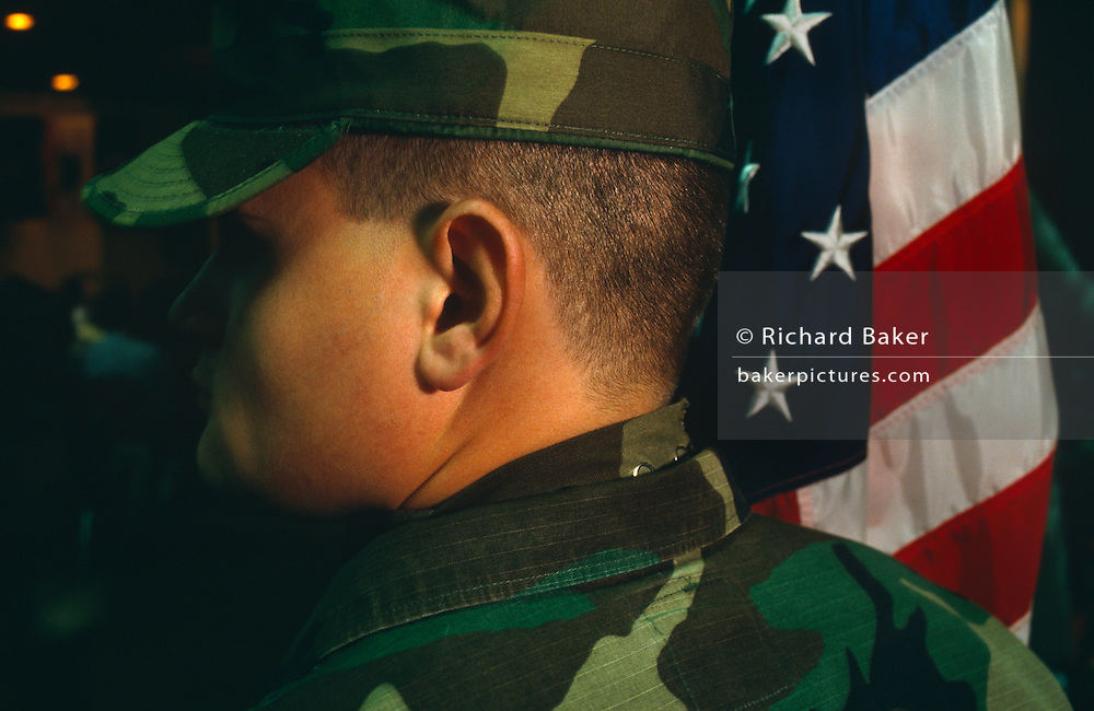 We see the head and shoulders of a man in military uniform who stands motionless beside the American flag.  he is at a graduation ceremony for United States Air Force pilots who have just passed a week-long survival courseheld at the Fairchild Air Force Base, Spokane, Washington. Its highy-trained personel conducts a survival, escape and evasion course which combat pilots and air crew need to pass before rejoining their units for real-time warfare. Conducted, in hangars and the surrounding forests, it forms part of an extensive physical and psychological assessment of young aviators on active service. In the future any one of them may be shot down behind enemy lines and need to use the lessons passed-on here to help facilitate their rescue by US forces. One pilot who passed this course in 1991, himself a Spokane-born boy, was F-16 pilot Scott O'Grady. He put his skills learned here to the test while evading Serb forces before being airlifted to safety and a hero's Presidential welcome.