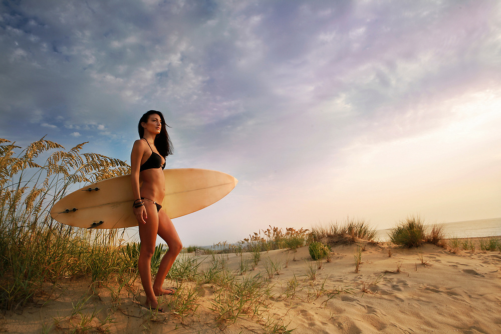 Girl on sand dunes with surf board