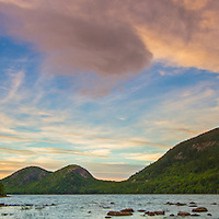 Maine panorama photography prints of Jordan Pond in the early fall as seen shortly before sunset. This beautiful pond is in the heart of Acadia National Park on Mount Desert Island and one of the top photo hot spots for waterscape photography. The shore line and rocks in the foreground provide interesting compositional elements while leading the viewer towards the South and North Bubbles in the back of the frame. <br />