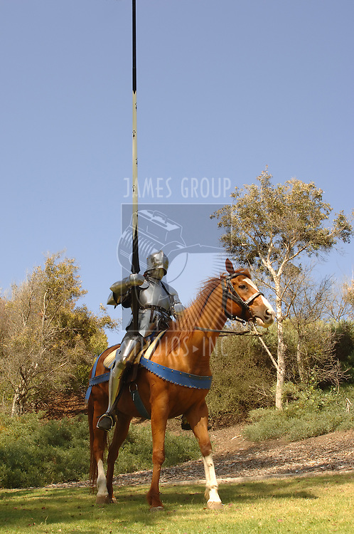 vertical full shot of 15th century knight in shining armour holding lance on horseback