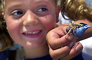 OCEAN CITY, NJ - JULY 31:  Natalie Knause, 5, of Swarthmore, Pennsylvania, looks at her hermit crab, Dave Jr., as a family member holds him, after he competed at the 27th Annual Miss Crustacean Beauty Pageant, July 31, in Ocean City, New Jersey. Children from all over the U.S. come to compete in what is billed as the world's only beauty pageant for hermit crabs. Each entry has a theme, and a set for it's respective crab or crabs. (Photo by William Thomas Cain/Getty Images)