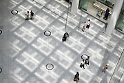 overhead view of people walking on a public space floor with light from roof pattern