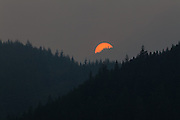 The sun sets behind a haze of smoke and coast mountains during the high forest fire season of summer 2015 in Squamish, British Columbia