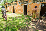 29 OCTOBER 2012 - MAYO, PATTANI, THAILAND:  A trustee passes a resident in shackles at the Bukit Kong home in Mayo, Pattani. The home opened 27 years ago as a ponoh school, or traditional Islamic school, in the Mayo district of Pattani. Shortly after it opened, people asked the headmaster to look after individuals with mental illness. The headmaster took them in and soon the school was a home for the mentally ill. Thailand has limited mental health facilities and most are in Bangkok, more than 1,100 kilometers (650 miles) away. The founder died suddenly in 2006 and now his widow, Nuriah Jeteh, struggles to keep the home open. Facilities are crude by western standards but the people who live here have nowhere else to go. Some were brought here by family, others dropped off by the military or police. The home relies on donations and gets no official government support, although soldiers occasionally drop off food. Now there are only six patients, three of whom are kept chained in their rooms.  Jeteh says she relies on traditional Muslim prayers, holy water and herbal medicines to treat the residents. Western style drugs are not available and they don't have a medic on staff.    PHOTO BY JACK KURTZ