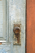 old rusty doorknob and keyhole on door with peeling paint