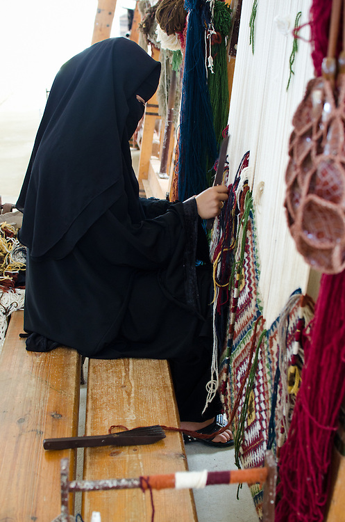 A Bedouin woman weaves at a small scale rug factory in Marsa Matruh, Egypt, where she earns less than $2 per day.