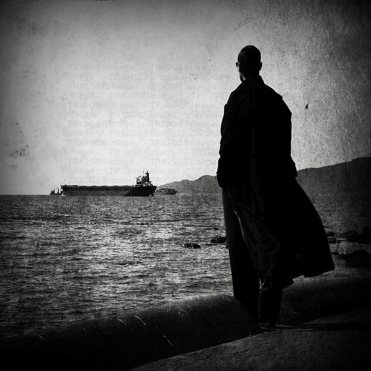 A man wearing a long overcoat looking out to sea