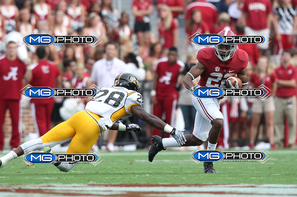 Sep 13, 2014; Tuscaloosa, AL, USA; Southern Miss Golden Eagles defensive back Jacorius Cotton (28) reaches out for Alabama Crimson Tide wide receiver Christion Jones (22) during a punt return at Bryant-Denny Stadium. Mandatory Credit: Marvin Gentry-USA TODAY Sports