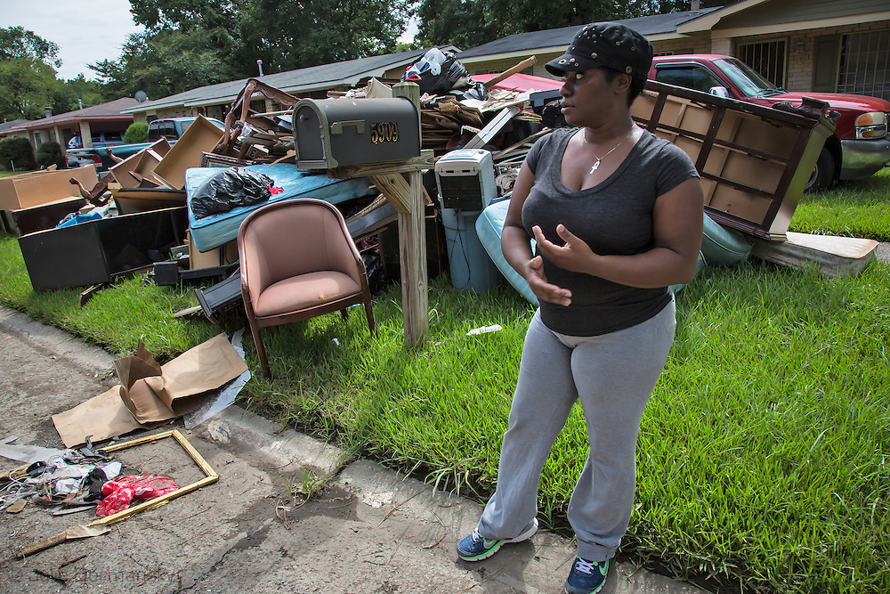 Roxanna Johnson in front of her flooded home in East Fariline, a subdivision in Baton Rouge, surveying her block.