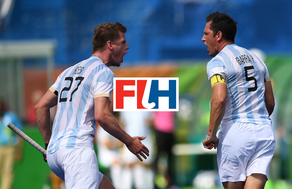 Argentina's Lucas Rossi (L) celebrates after Argentina's Pedro Ibarra (R) scored a goal during the men's field hockey Argentina vs Germany match of the Rio 2016 Olympics Games at the Olympic Hockey Centre in Rio de Janeiro on August, 11 2016. / AFP / MANAN VATSYAYANA        (Photo credit should read MANAN VATSYAYANA/AFP/Getty Images)