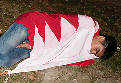 © under license to London News Pictures. 20/02/2011. A young man sleeps  at Pearl Roundabout in Manama, Bahrain wrapped in the Bahrain last night (19/02/2011). Photo credit should read Michael Graae/London News Pictures