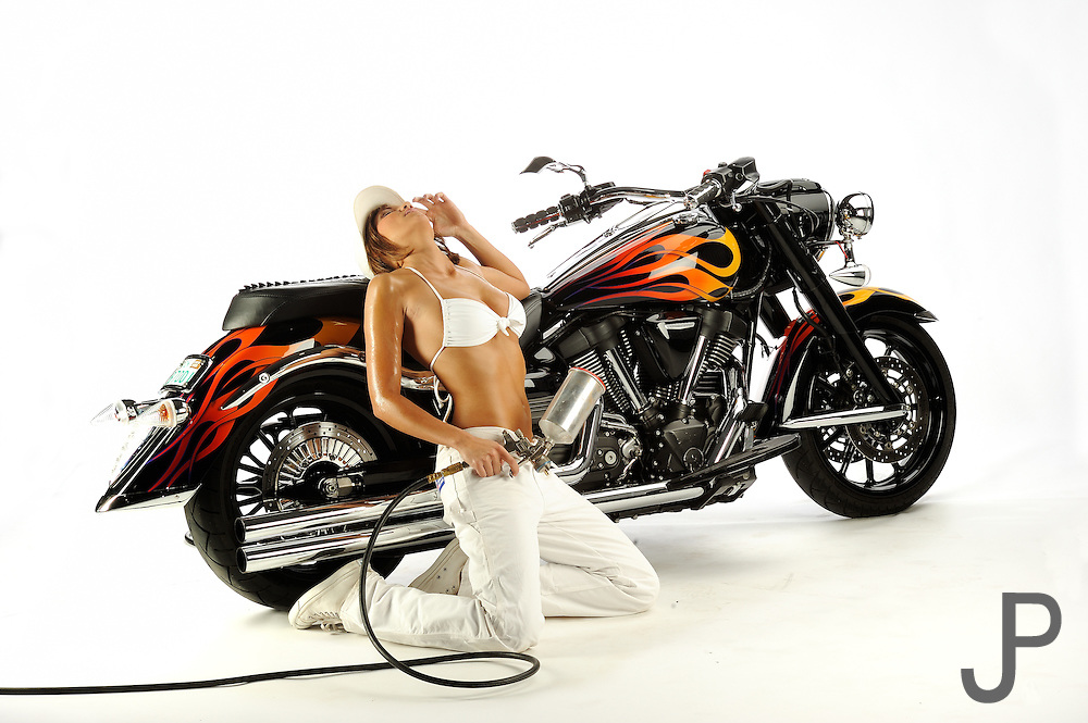 Model Crystal Peak in painter outfit painting Tommy Bolton's Yamaha Warrior motorcycle