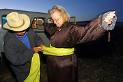 GOBI DESERT, MONGOLIA..08/25/2001.Gobi Gurvansaikhan National Park..Khongoryn Els sand dunes. Jeep driver of Nomads Tours having fun with dressing a passenger in a traditional del..(Photo by Heimo Aga).