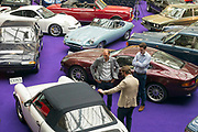 UNITED KINGDOM, London: 24 April 2018 Visitors make their way through a collection of classic cars inside The Royal Horticultural Halls, Westminster. The cars form part of the Spring Classics: An Important Auction of Fine Historic Automobiles at The Royal Horticultural Halls, Westminster. The auction will see a collection of privately owned cars be auctioned this evening April 24th 2018. Rick Findler  / Story Picture Agency