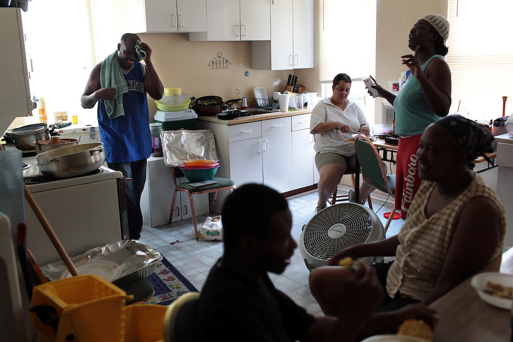Pastor William Horne, left, has lunch with (from left) Assistant Pastor Shelvy Clark, foreground, Kimberly Robinson, background, Salone Williams, 26, right and Apostle Jasmine Clark, far right foreground, at his home in Baltimore, MD on August 8, 2010. William Horne lost his home in a rent-back scheme and is currently suing the company. For ProPublica on the Baltimore foreclosure story. .Photographer: Melanie Burford for ProPublica.